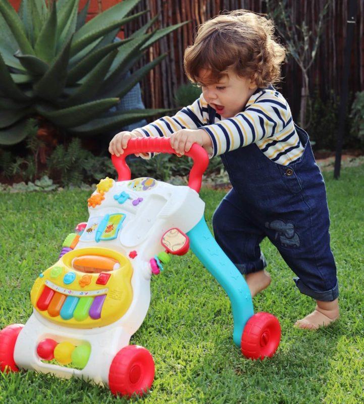 baby pushing walker outside