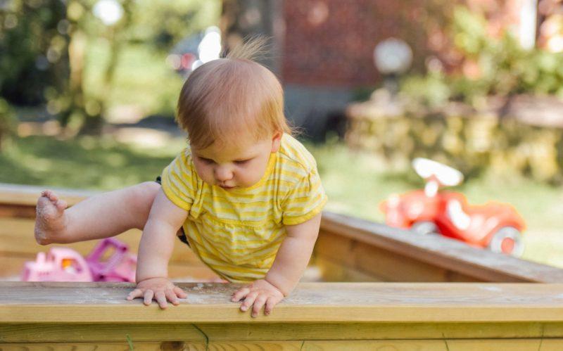 toddler climbing in sandbox